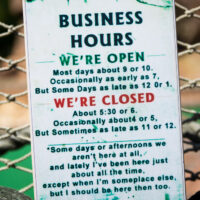 Business Hours Sign, white with green black and red lettering. Lighthearted look at business hours in the Keys