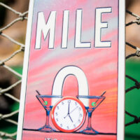 Mile 0 sign two martini glasses with a clock at 5 O'clock