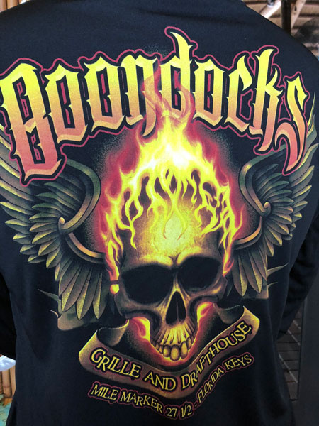 Graphic on the back of the long sleeve black biker T-Shirt. Flamming Skull with wings behind it. Boondocks in large yellow fading to orange lettering across the top. Scroll like ribbon across the bottom reading Grille & Draft House, Mile Marker 27.5 Ramrod Key.