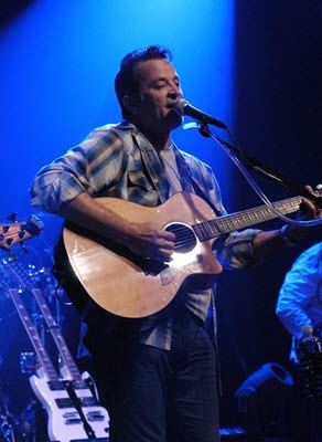 Greg Pitts playing acoustic guitar on stage